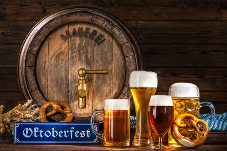 Oktoberfest beer barrel with beer mugs and pretzels on wooden background Stock Photo