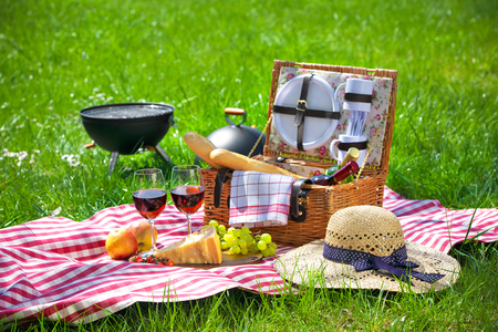 hamper: Picnic setting with red wine glasses, picnic hamper basket and burning fire in a portable barbecue