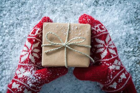 Mani femminili in guanti invernali con confezione regalo di natale Archivio Fotografico - 57058431