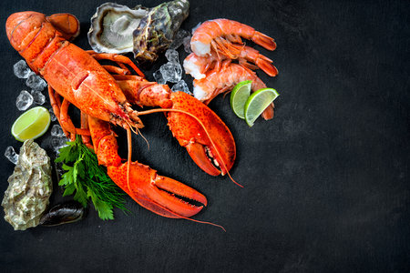 Shellfish plate of crustacean seafood with fresh lobster, mussels, shrimps, oysters as an ocean gourmet dinner background Stok Fotoğraf