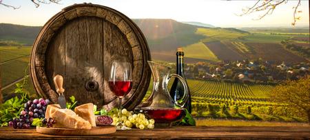 Barril con el cristal de vino tinto y el queso en el viñedo Foto de archivo - 57058457