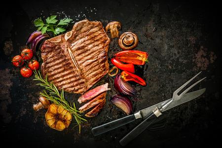 seasoning: Beef T-Bone steak with grilled vegetables and seasoning on dark background