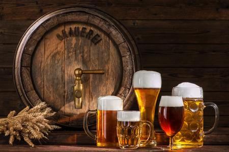 木製の背景にビールのグラスをビール樽