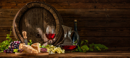 Still life with glass of red wine and old oak wine barrel