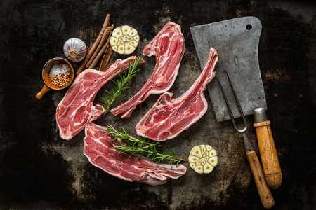 Raw fresh lamb meat and meat cleaver and fork on dark background