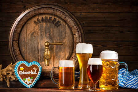 Oktoberfest. Beer barrel with beer mugs and a heart shaped gingerbread on wooden background