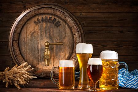 vasos de cerveza: Barril de cerveza con vasos de cerveza en el fondo de madera
