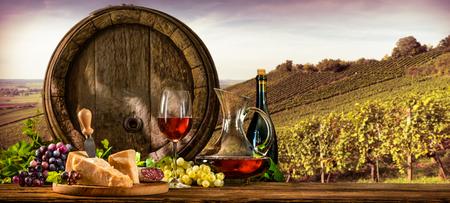 Barril con el cristal de vino tinto y el queso en el viñedo Foto de archivo - 57058860