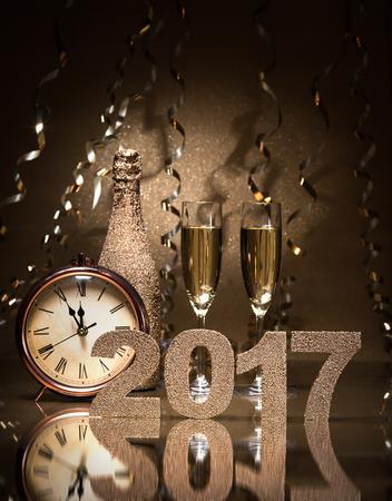 Capodanno celebrazione sfondo con coppia di flauti, bottiglia di champagne e un orologio Archivio Fotografico - 57058876