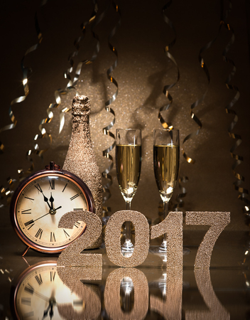 new year eve: New Years Eve celebration background with pair of flutes, bottle of champagne and a clock Stock Photo