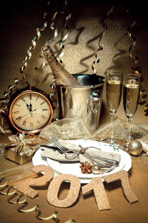eve: New year holiday table setting with champagne. Celebration. Place setting for new year eve. Holiday decorations. Served table Stock Photo
