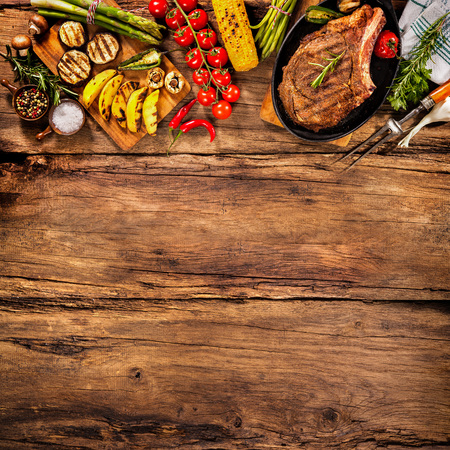 garnish: Beef steak with grilled vegetables and seasoning on wood Stock Photo