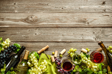Bottiglie di vino con l'uva, formaggi e salumi tradizionali su fondo in legno con spazio di copia Archivio Fotografico - 57806493