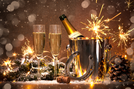 champagne flute: New Years Eve celebration background with pair of flutes and bottle of champagne in  bucket  and a horseshoe as lucky charm
