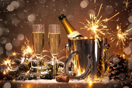 flauta: Nochevieja fondo de la celebración con pares de flautas y botella de champán en un cubo y una herradura como amuleto de la suerte