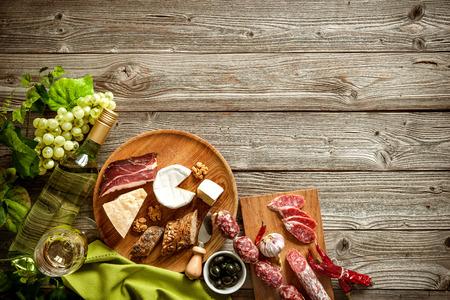 pan frances: Botellas de vino con uvas, queso y salchichas tradicionales sobre fondo de madera con espacio de copia