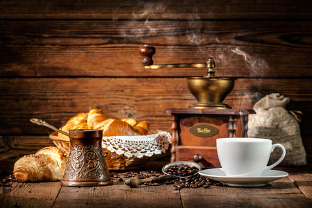 taza cafe: Taza de café con croissants y granos de café en el fondo de madera