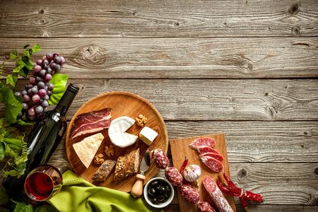 Wijnflessen met druiven, kaas en traditionele worsten op houten achtergrond met een kopie ruimte Stockfoto