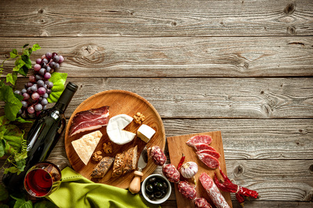 view from the above: Wine bottles with grapes, cheese and traditional sausages on wooden background with copy space