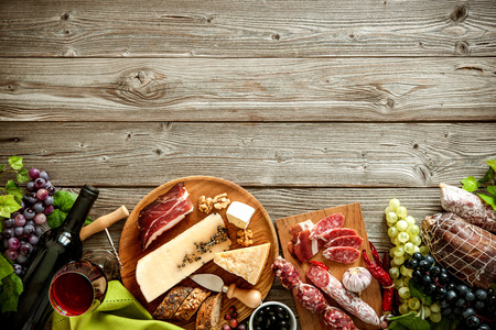 Botellas de vino con uvas, queso y salchichas tradicionales sobre fondo de madera con espacio de copia Foto de archivo - 57806604