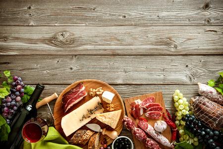 Bottiglie di vino con l'uva, formaggi e salumi tradizionali su fondo in legno con spazio di copia Archivio Fotografico - 57806604