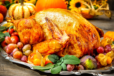 Thanksgiving dinner. Roasted turkey on holiday table with pumpkins, flowers and wine