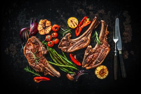 Roasted lamb meat with vegetables on dark background Standard-Bild