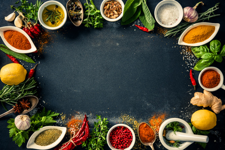 seasoning: Herbs and spices over black stone background. Top view with copy space