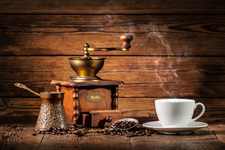 bracing: Coffee grinder, turk and cup of coffee on brown wooden background Stock Photo
