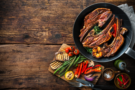 black dish: Roasted lamb meat with vegetables on grill pan on wooden background Stock Photo