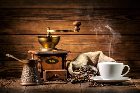 Coffee grinder, turk and cup of coffee on brown wooden background Stock Photo
