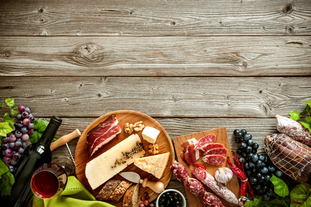 jamon y queso: Botellas de vino con uvas, queso y salchichas tradicionales sobre fondo de madera con espacio de copia