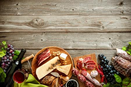 Bottiglie di vino con l'uva, formaggi e salumi tradizionali su fondo in legno con spazio di copia Archivio Fotografico - 57807069