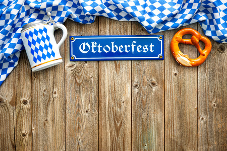 ババリア地方の白と青のファブリック、ビール ジョッキ柔らかいプレッツェルとオクトーバーフェストの素朴な背景