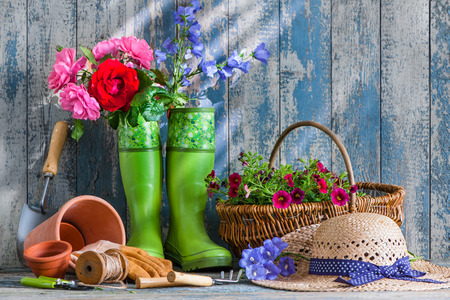 straw hat: Gardening tools and flowers on the terrace in the garden Stock Photo