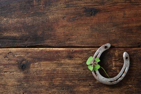 Old horse shoe,with clover leaf, on wooden background Standard-Bild