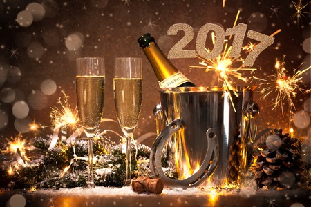 greeting season: New Years Eve celebration background with pair of flutes and bottle of champagne in  bucket  and a horseshoe as lucky charm