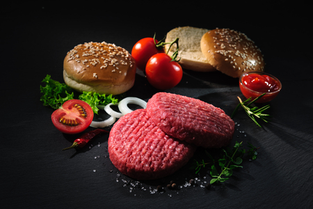 Homemade hamburger. Raw beef patties, sesame buns with other ingredients for hamburgers on dark slate plate Stok Fotoğraf - 64054939