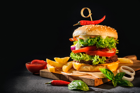 Delicious hamburgers with french fries on dark background Stockfoto