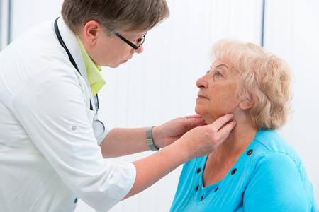 La funzione tiroidea esame. Medico toccando la gola di un paziente in ufficio Archivio Fotografico - 60368122