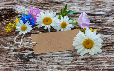 flores de cumpleaños: Wild Flowers with a vintage tag on wooden background