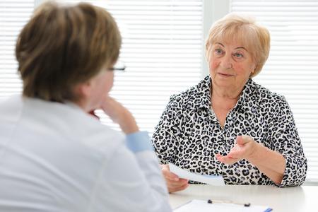 Vrouwelijke oudste patiënt vertelt de dokter over haar gezondheidsklachten Stockfoto