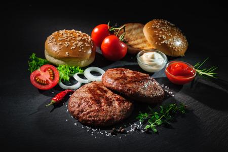Zelfgemaakte hamburger. Gegrild rundvlees pasteitjes, sesam broodjes met andere ingrediënten voor hamburgers op donkere leisteen plaat Stockfoto