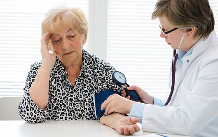 hypotension: Doctor checking elderly womans blood pressure Stock Photo