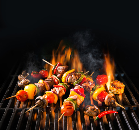 Grillspieße Fleischspieße mit Gemüse auf lodernden Grill