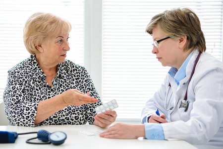 complaining: Mature woman complaining to doctor about prescribed drugs Stock Photo