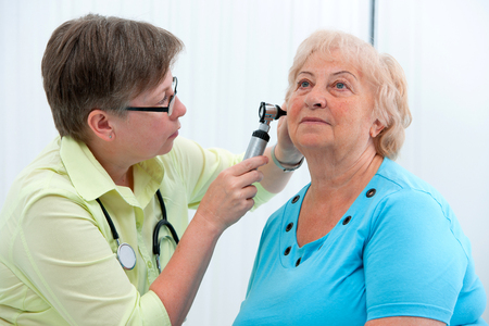 checkup: Ear examination. ENT physician looking into patients ear with an instrument Stock Photo