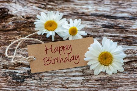 Flores de margarita con una etiqueta feliz cumpleaños en el fondo de madera Foto de archivo - 61852274