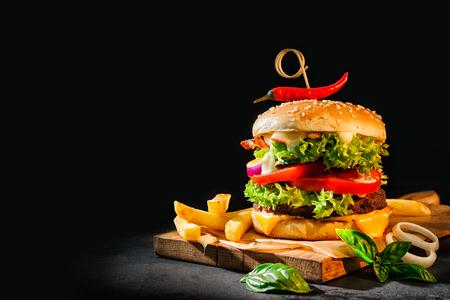 暗い背景にフライド ポテトおいしいハンバーガー 写真素材