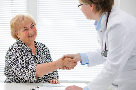 general practice: Doctor shaking hands with patient in the office